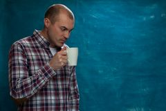 Serious man wearing plaid shirt posing. With coffee mug in hands against blue background Stock Image