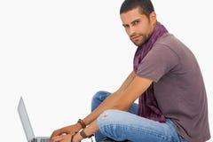 Serious man wearing scarf sitting on floor using laptop Stock Photos