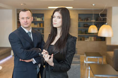 Serious man and woman standing with a notepad Stock Image