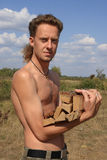Serious man with woodpile. Attractive man with woodpile. Side view. Man looking us Royalty Free Stock Photos