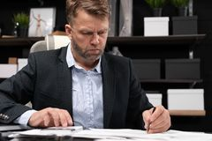 Businessman sitting at computer Desk and thinking about documents. Serious man working with business papers in modern stylish office. Portrait of businessman in royalty free stock photo