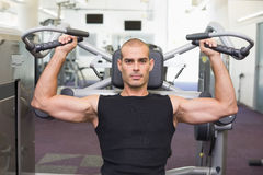 Serious man working on fitness machine at gym Royalty Free Stock Photography