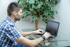 Serious man working at a laptop at home. A man sitting at a glass table. He is dressed in a shirt and jeans. Wristwatch on the hand Royalty Free Stock Photo