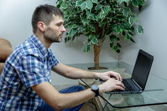 Serious man working at a laptop at home. A man sitting at a glass table. He is dressed in a shirt and jeans. Wristwatch on the hand Stock Photos