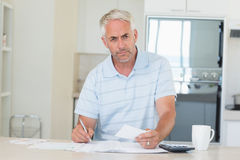 Serious man working out his finances Stock Image