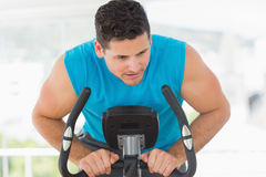 Serious man working out at spinning class Stock Photos