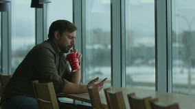 Serious man writes a message and drinks, by a large window. stock footage