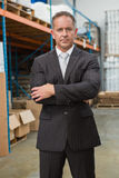 Serious manager with arms crossed in warehouse Royalty Free Stock Image