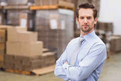 Serious manager with arms crossed in warehouse Stock Image