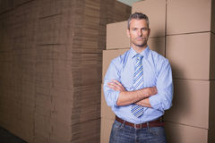 Serious manager with arms crossed in warehouse Stock Images