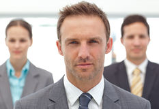 Serious manager posing in front of his colleagues Stock Image