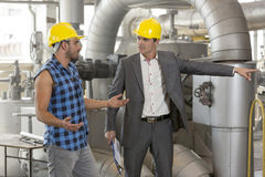 Serious manager showing something to worker in industry Stock Images