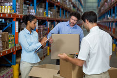 Serious managers are checking some cardboard boxes. In a warehouse stock image