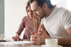 Serious married couple with papers, considering loan offer, calc. Serious couple studying contract agreement, reading terms and conditions attentively before Stock Photography