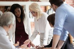 Serious mature business woman supervisor teaching workers at group meeting