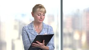 Serious mature business woman writing on clipboard. Bright blurred background stock footage