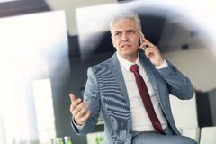 Serious mature businessman talking on mobile phone in office Royalty Free Stock Photos