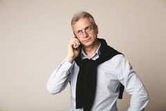 Serious mature businessman talking on mobile phone. Over light background stock photos