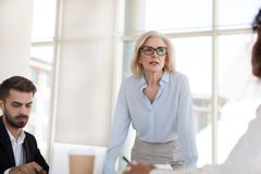Serious mature businesswoman talk having discussion during brief. Serious mature businesswoman stand talk with employees at office meeting, middle aged female royalty free stock photography
