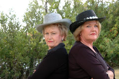 Serious mature country women. Mature woman cowboy hats outdoors back to back with serious looks Royalty Free Stock Photo