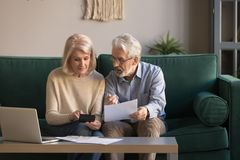 Serious mature couple calculating bills, checking domestic finances. Serious mature couple calculating bills to pay, checking domestic finances, middle aged royalty free stock photos