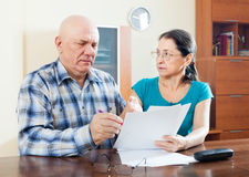Serious mature couple fills in questionnaire Royalty Free Stock Photos