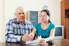 Serious mature couple fills in questionnaire Royalty Free Stock Photo