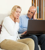 Serious mature couple  with laptop Royalty Free Stock Photos