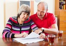 Serious mature couple reading  document Stock Photo