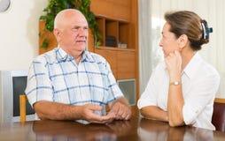Serious mature couple talking Stock Image