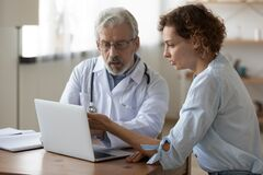 Free Serious Mature Doctor Showing Checkup Result On Laptop To Patient Royalty Free Stock Photo - 194862055