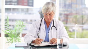 Serious mature doctor writing on her calendar stock video