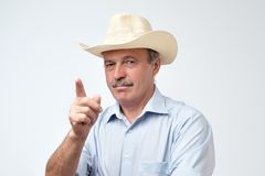 Serious mature hispanic man in cowboy hat showing index fingers up, giving advice or recommendation stock photography