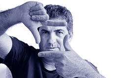 Serious mature man creating frame with fingers. Serious one young mature man only creating frame with fingers.Copy space on white background. real people stock images