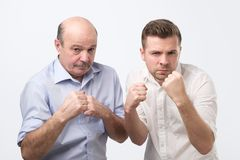 Serious mature man and his adult son keep hands in fists in protective or defensive gesture. Serious mature men and his adult son keep hands in fists in royalty free stock photography