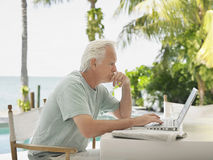Serious Mature Man Using Laptop Outdoors. Side view of a serious mature man using laptop at outdoor table Stock Image