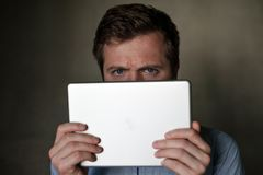 Serious mature middle aged man looking into tablet and frown his face. Royalty Free Stock Image
