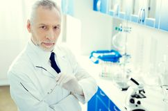 Serious mature researcher posing and looking into camera. Experienced professional. Top view on a confident scientist holding his glasses and looking into the Royalty Free Stock Photography