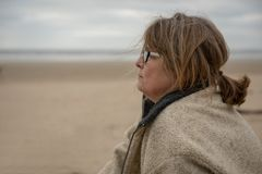 Serious mature woman on the beach stock photography