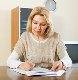 Serious mature woman with financial documents Royalty Free Stock Photos