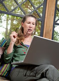Serious Mature Woman at Home at Laptop Computer Stock Photography