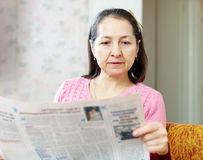 Serious  woman reading newspaper Royalty Free Stock Photo