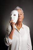 Serious mature woman revealing face behind mask. Serious looking mature woman revealing true face behind mask Stock Photo