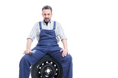 Serious mechanic with spanner sitting on car tire Royalty Free Stock Photo