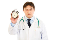Serious medical doctor holding alarm clock in hand Royalty Free Stock Images