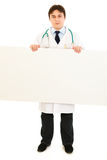 Serious medical doctor holding blank billboard Royalty Free Stock Photo