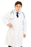 Serious medical doctor putting money in pocket Royalty Free Stock Image