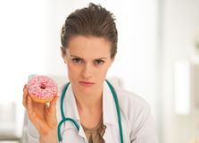 Serious medical doctor woman showing donut Stock Image