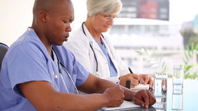 Serious medical people writing on their notepads Stock Photography