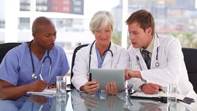 Serious medical team looking at a tablet computer Stock Photo